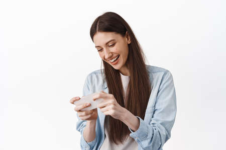 Happy young woman playing video game on smartphone, laughing and looking at phone screen, enjoying gaming, standing against white background