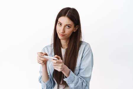 Image of bored and gloomy girl, look from under forehead while using her phone, playing boring game, watching uninteresting video online on smartphone, standing over white background 版權商用圖片
