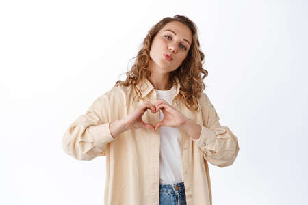 Portrait of young blond woman with curly hair, showing love heart gesture, pucker lips, say I love you, express admiration, making kissing face, white background