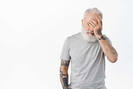 Oh gosh. Tired and annoyed senior man facepalm, hold hand on face distressed or exhausted, standing irritated in casual grey t-shirt against white background
