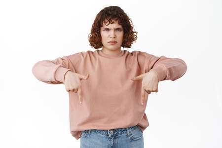 Angry frowned young girl complains, pointing fingers down with sulking upset face, disappointed, standing against white background