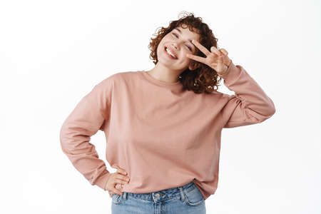 Upbeat beautiful girl, tilt head and smile coy, shows peace  v-sign near eye, looking joyful and positive, standing over white background