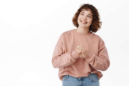 Happy authentic girl smiling, looking at upper left corner promo logo, reading advertisement with cheerful pleased face, daydreaming, standing over white background