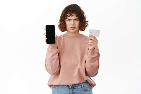Online shopping. Angry young woman frowning, showing credit card and empty smartphone screen, disappointed in mobile phone application, standing upset against white background Stock fotó
