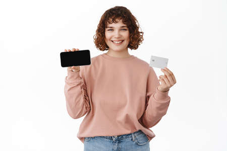 Online shopping and mobile banking. Happy attractive woman showing horizontal smartphone screen with bank credit card, recommending mobile app, standing against white background