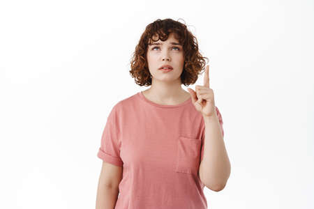 Puzzled young woman raising eyebrows hesitant, pointing and looking up with doubtful questioned face, reading advertisement on top, standing in t-shirt against white background Stock fotó