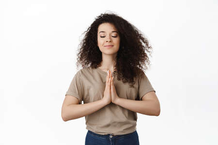 Calm young woman meditating, show namaste pray gesture, close eyes and smiling, making wish, pleading god, standing over white background