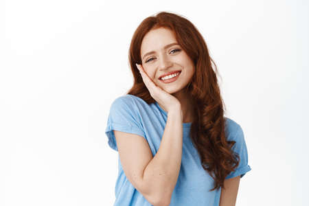 Adorable young woman with fresh and clean natural skin, red hair, touching cheek and smiling happy and satisfied, using cleansing facial skincare cosmetic, standing over white background