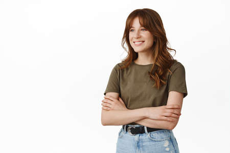 Image of stylish young woman in t-shirt, cross arms on chest, standing relaxed and natural, looking aside as if talking with someone, white background
