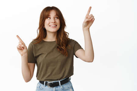 Smiling female customer, girl making choice, pointing sideways and looking at upper right variant, clicking on banner, standing happy against white background Banco de Imagens