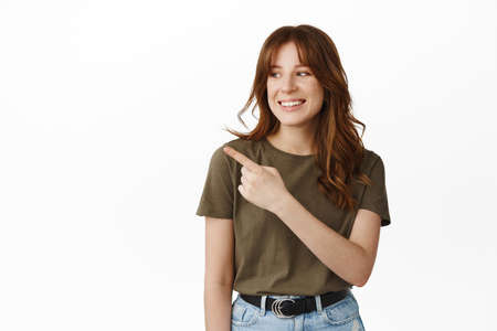 Cheerful young teenage girl pointing and looking left at promo offer, showing advertisement, demonstrating promotional text on empty white background