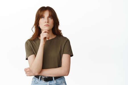 Image of girl student thinking, making choice, looking up and frowning perplexed, pondering decision, standing thoughtful against white background.