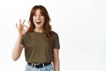 Very good, awesome. Smiling happy girl showing OK okay sign, say yes and looking amazed, praise choice, making compliment, positive feedback, standing against white background