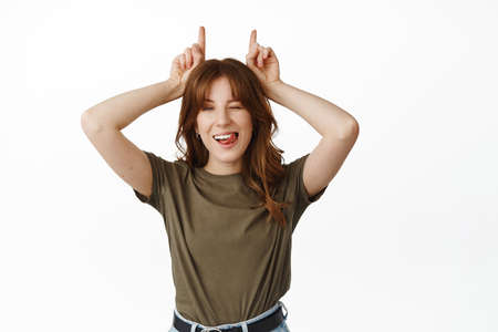 Cheeky young woman winking, showing tongue and smiling, making bull horns gesture above head, standing funny and playful against white background Banco de Imagens