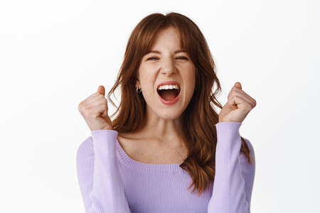 Portrait of happy young woman celebrating, shouting yes with rejoice and happiness, fist pump from excitement, triumphing with joy, standing over white background