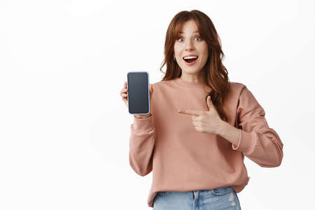 Portrait of cheerful girl gasp amazed, pointing finger at smartphone screen, showing online shop, store or application for mobile phone, standing over white background