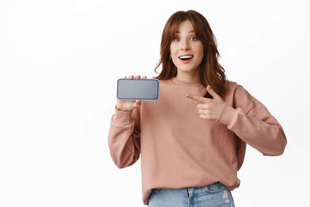 Excited redhead girl show app or mobile video game, pointing finger at smartphone application, smiling amazed, standing over white background