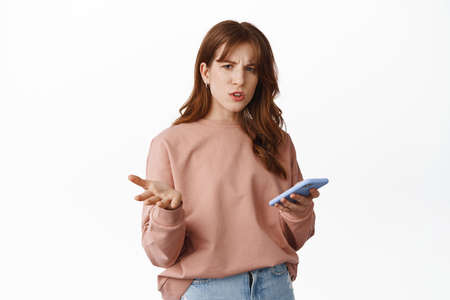 Portrait of redhead woman confused with smartphone, staring questioned and holding mobile phone, standing against white background