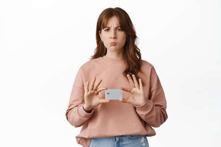 Portrait of young woman bank client, looks disappointed and pouting, shows credit card upset, stands against white background Banco de Imagens