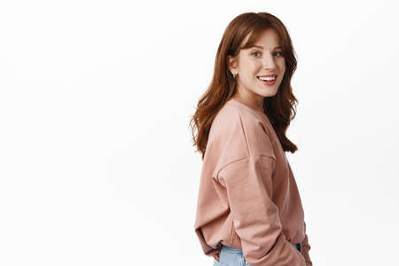 Wellbeing and people concept. Portrait of young smiling redhead woman turn head at camera, stands in profile, looking happy and friendly, standing against white background