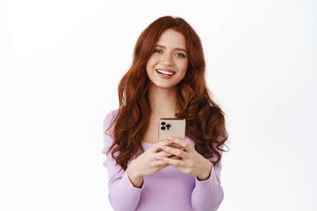 Smiling ginger girl chatting, holding smartphone as if shopping online, looking happy while messaging, standing in blouse against white background