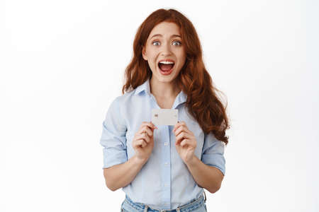 Portrait of amazed redhead woman bank client, showing credit card and gasping astonished, telling about discounts, contactless payment, banking promotion, standing against white background