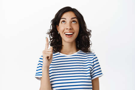 Smiling natural woman with dark curly hair, pierced nose, laughing and looking happy at top advertisement, pointing finger up, showing promotion text, white background Banco de Imagens