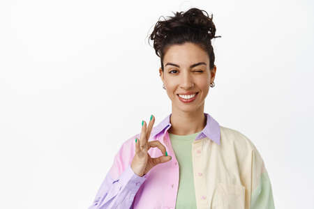 Cheerful brunette girl smiling satisfied, showing zero okay sign, ok gesture and winking, assure everything under control, all good, standing pleased against white background