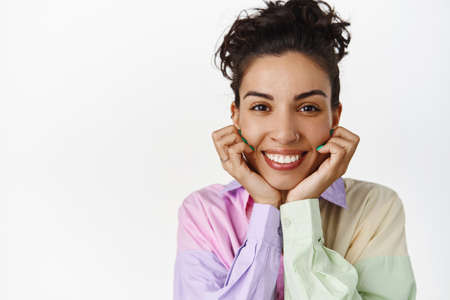 Close up face portrait of smiling happy woman, hold hands on face, looking at camera with satisfied cheerful face, watch something interesting, white background