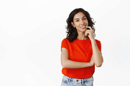 Stylish brunette girl with curly hairstyle, red t-shirt, biting finger coquettish while thinking, making choice or decision, standing over white background Banco de Imagens