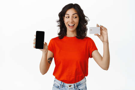 Cheerful girl student paying online, shows credit card of bank, moble phone screen, smiling happy and satisfied, shopping in application, white background