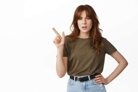 Skeptical young woman shaking finger disapprove, dislike something, pointing at upper left corner with upset grimace, frowning doubtful, standing over white background
