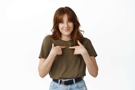 Cute shy girl pointing at herself, smiling pleased, winning, self-promoting, this is me gesture, standing against white background