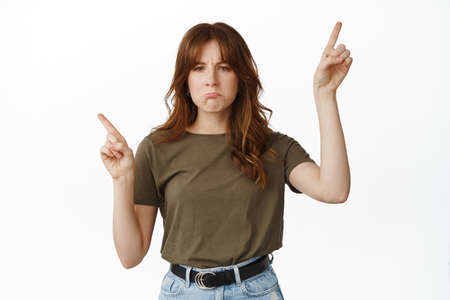 Sad and gloomy teenage girl sulking, pointing sideways with regret, being jealous about something, complain, standing against white background