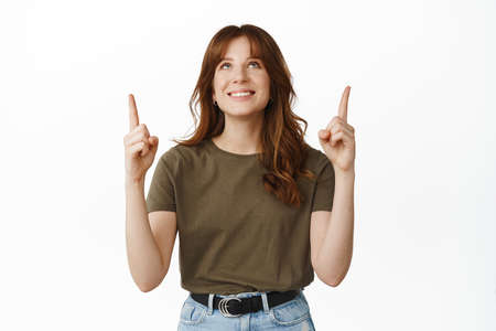 Image of happy dreamy woman looking and pointing fingers up, reading banner upwards, showing promotional text on top, pleased by promo, standing against white background