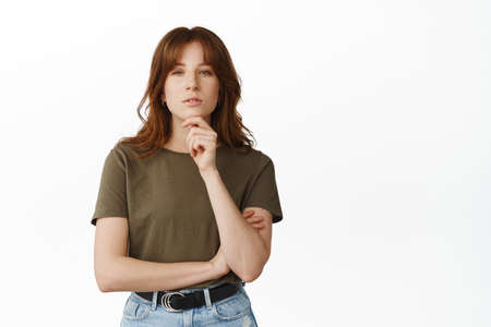 Thoughtful young woman listening with interest, touch chin while thinking, looking at camera with curious face, making decision, standing in t-shirt against white background