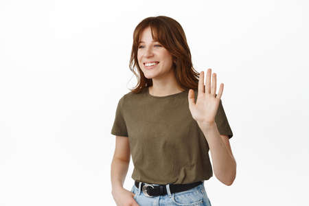 Image of modern girl waving hand, saying hello, raising palm to make hi gesture, smiling and looking friendly aside, meeting friend, standing against white background