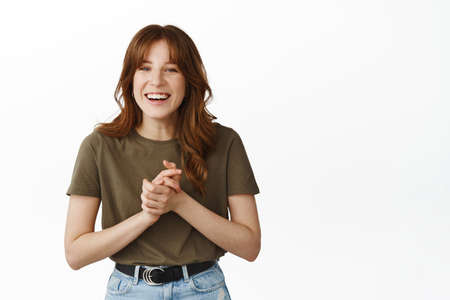 Thankful and happy young woman, clench hands and smiling grateful, appreciate something, receive prize, thank you gesture, standing over white background flattered
