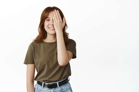 Happy smiling girl cover half of face with hand, looking cheerful, hiding one eye, checking sight in eyewear store, standing over white background