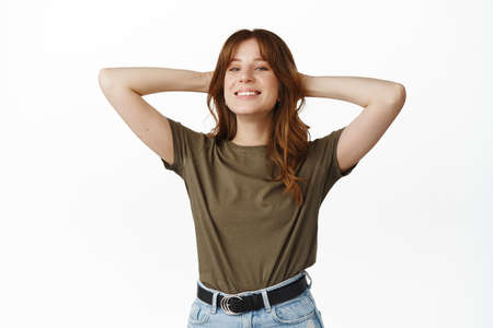 Carefree and relaxed redhead girl smiling satisfied, holding hands behind head pleased, enjoying leisure time, resting after work done, standing over white background