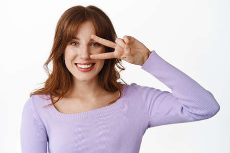 Close up of beautiful, stylish woman with bangs, freckles and white teeth, showing peace v-sign near eye, smiling happy at camera, standing against white background Banco de Imagens