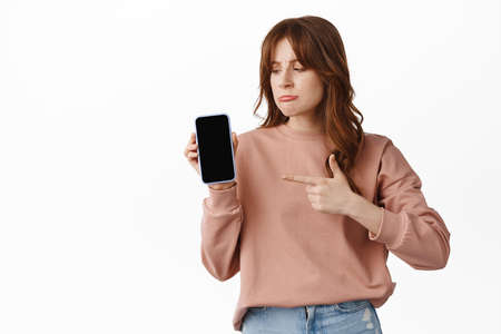 Upset frowning girl pointing finger at smartphoe screen, showing advertisement on phone and looking sad, complaining, feel regret or jealousy, standing over white background Banco de Imagens