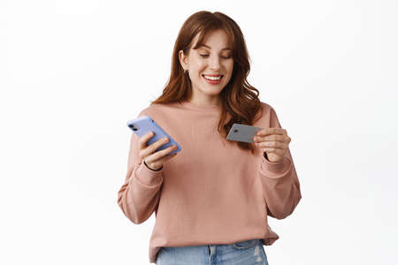 Online shopping. Smiling redhead girl looking at credit card, holding smartphone, paying for order, checking bank account, standing over white background