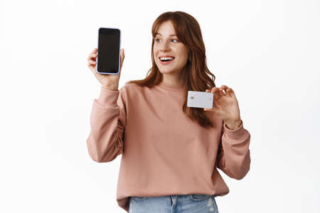 Image of cheerful ginger girl looks at smartphone, shows empty phone screen an credit card with pleased smile, online shopping, app and technology concept