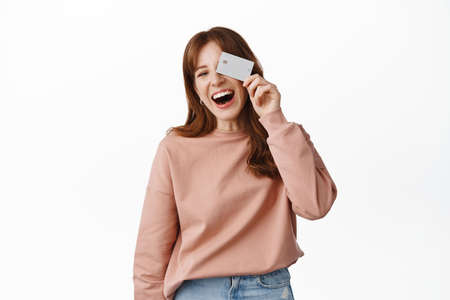 Image of happy ginger girl laughs, shows credit card, paying for purchase contactless, going shopping, recommend bank, standing over white background