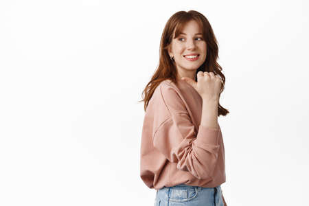 Image of stylish redhead teen girl, look behind her shoulder and smiling, pointing finger left at copy space advertisement, standing against white background