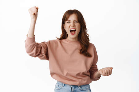Excited redhead girl celebrating, cheering and rooting for team, triumphing of victory, scream amazed, winning something, achieve goal or success, standing over white background