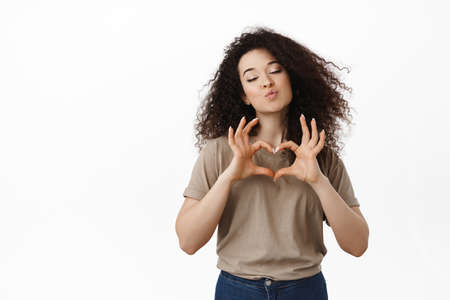 Flirty brunette girl falls in love, shows heart sign and kissing lips, standing romantic and dreamy against white background
