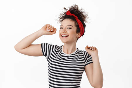 Carefree attractive woman in headband, dancing and having fun, smiling and laughing relaxed, resting at party, standing against white background