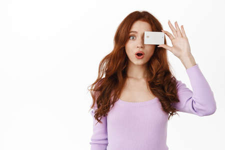 Amazed ginger girl gasp and say wow, show bank credit card near eye, advertising shopping promotion, standing in blouse against white background